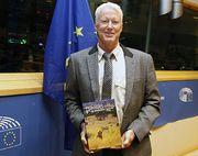 Kai Uwe Denker, Vorsitzender des EMRST und Sahreman des Erongo Verzeichnisses für afrikanisches Jagdwild mit seinem Buch vor der europäischen Fahne im Sitzungssaal des Brüsseler Parlaments